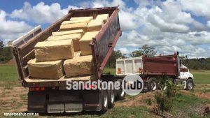 Sandstone Blocks Logs Being Unloaded From Tip Truck