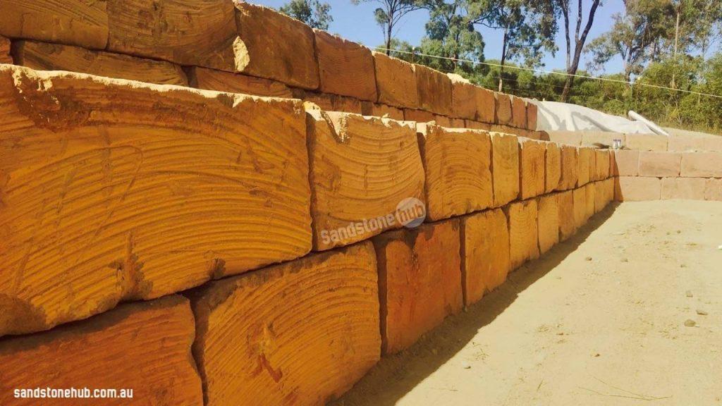 Sandstone Retaining Wall Under Construction With Orange Wheel Sawn Blocks